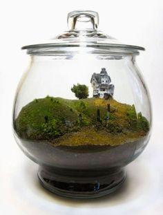 Como uma fazenda em miniatura, este terrário leva grama, miniatura de árvore e um casarão.