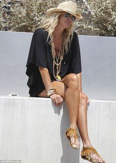 Sitting pretty: Elle was later seen soaking up the sunshine as she perched on a wall in the port