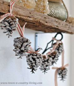 Frosted pine cones strung across a shelf will make any home feel like a cabin in the woods.Get the t... - Courtesy of Town and Country Living