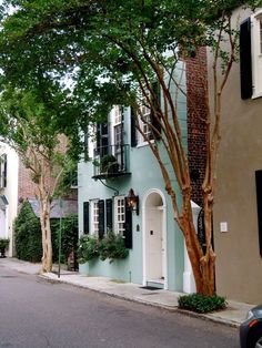 Minty turquoise blue / green painted house exterior with black shutters in Charleston, South Carolina