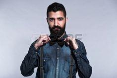 Retro hipster 1900 mode man met zwart haar en baard Gekleed in een blauwe jeans overhemd strikje Stu Stockfoto