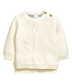 Natural white. Purl-knit sweater in soft cotton with a motif at front and buttons on one shoulder. Ribbing at neckline, cuffs, and hem and short slits at