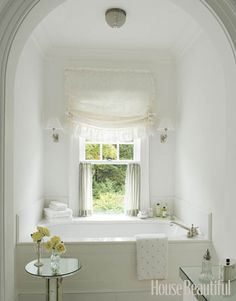 i love the frilly window treatment and the petite light fixtures on either side, as well as the placement of the tub in the pretty alcove.  so feminine!