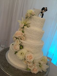 4 tier round buttercream wedding cake with scrollwork and cascading flowers