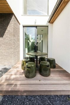 outdoor dining area ideas contain a round dining table surrounded by six dining stools in dark green