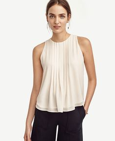 "Sheer romance: One of the season's A-list pieces, our crisp pintucked top refines any ensemble with bespoke beauty. Jewel neck. Sleeveless. Box pleated front and back. Back keyhole with button closure. Hi-lo shirttail hem. Lined. 21"" front length; 25 1/4"" back length."
