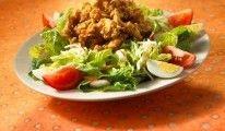 CAJUN FRIED CHICKEN SALAD Knusprig gebackene Hühnerbruststreifen auf Blattsalat, mit Tomaten, hartgekochtem Ei, Monterey Jack Käse und Honey Mustard Dressing.