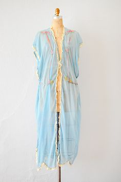 1920's sky blue lingerie robe is decorated with pastel floral embroidery along the front with long silken ribbons along the front that can be tied in the back or front. Lace trims along the front.