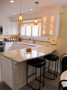 traditional white kitchen design with peninsula granite countertop