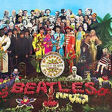 """The Beatles, holding marching band instruments and wearing colourful uniforms, stand near a grave covered with flowers that spell """"Beatles"""". Standing behind the band are several dozen famous people."""