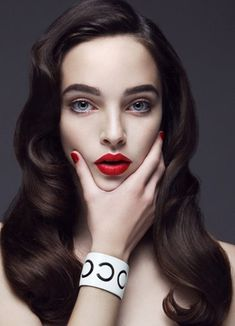 Red lips, pale skin, dark brown hair.