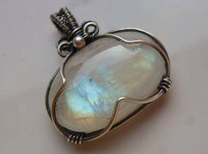Size Width 26 mm, Length approx. 28 mm Weight approx. 5.96 g The materials used 935 silver wire Rainbow Moonstone (white Labradorite) Silver solder (lead free) Method of production Lovingly crafted made - UNIKAT This pendant was coated with a patina of antique-looking and then
