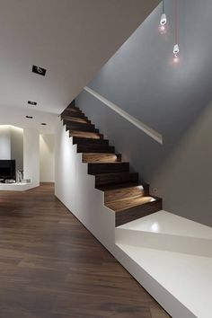 777...Well the dark, shiny wood flooring, must have inspired the white walls and staircase designs here. The two tone stairway, is different, and a darker wall on the right wall, going up, past the white entrance, to the shady staircase!