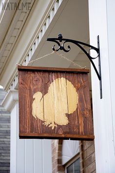 Use wood boards, tape paper picture (use double-sided tape underneath), and varnish on top. Hang outside for colonial look.