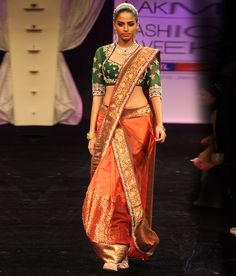 A beautiful draped ghagra in rust coloured silk with a dull green net dupatta draped over it. | Neeta Lulla Online Store