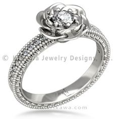 Vintage Rose Engagement Ring - This intricate engagement ring features a rose blossom with a prong-set center diamond or gemstone. The band has millegrained beading and pave-set diamonds. Shown with a 1/5 carat center stone.