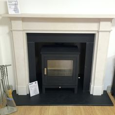 "Chesneys Shoreditch 8 stove in black with a Chesneys Devonshire 59"" mantel in Limestone on display in Corinium Stoves showroom in South Cerney, Gloucestershire"