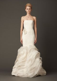 Floating corded leaf and embroidered circular lace strapless mermaid gown with bias organza and lace flange detail accented by crystal and pearl cluster embroidery at hip. Available in white, shown in ivory.