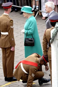 He stands after the Queen passes him. The monarch was not fazed as she knew that it was an act of respect