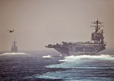 The aircraft carrier USS Abraham Lincoln (CVN 72), left, and the guided-missile cruiser USS Cape St. George (CG 71) transit the Strait of Hormuz., via Flickr.