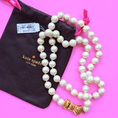 """Kate Spade New York Pearl & Bow Necklace ❌NO TRADES❌  - Kate Spade New York Pearl & Bow Necklace  - Large Cream White Iridescent Faux Pearls w/ Large Golden Bow Clasp    - Approx 15"""" length  - New with detached tag & dustbag kate spade Jewelry Necklaces"""