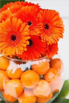 Tangerines in clear vase with matching flowers.