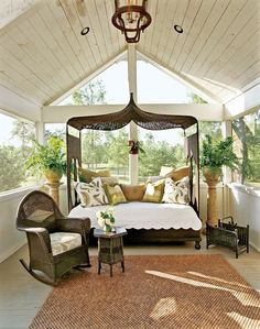 """An eco-friendly old-fashioned-style front porch required almost no new materials. The owners found two old half-round choir lofts and pieced them together. The """"witch's hat"""" peaked ceiling is a characteristic of Queen Anne architecture, which the remodeled ranch house emulates."""