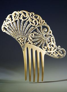 Very elegant asymmetrical shaped comb. Two reverse fan motifs are embellished with clear paste stones, circa 1925.