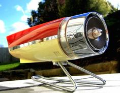 Sharp calls this 1959 Model BH-351 rocket radio the 'Tranket' derived from TRANsistor rocKET. It features sleek fins, streamlined contours, chrome accents, and a two tone red and white plastic body.  Its rear end resembles that of a 58 Buick.