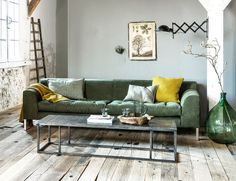 Industrial living room with pops of green and yellow and a wooden floor, green…