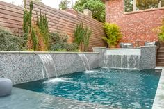 Raised wall with custom glass tile, two foot sheer descents, and spa with infinite edge spillway.