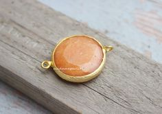 A personal favorite from my Etsy shop https://www.etsy.com/listing/218313123/peach-bezel-connector-35mm-matte-gold