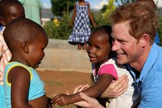 The relaxed royal, 30, is seen playing with delighted orphans and sick children during the trip to Lesotho with his AIDS charity Sentebale