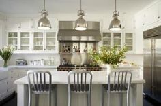 """Gorgeous kitchen design with glass-front cabinets, creamy white kitchen cabinets, white carrara marble counter tops, subway tiles backsplash, industrial yoke island pendants, 1006 Navy counter stools and stainless steel appliances"