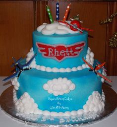 """Planes - 6"""" & 10"""" cakes iced in buttercream then sprayed with blue spray. Logo/name was done in fondant. Toppers are toys."""