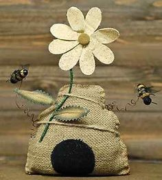 Stuffed burlap pillow in the shape of a beehive, accented with a fabric daisy, jute strings, and bees on curled rusty wires. The weighted bottom makes it a perfect addition to spring and garden-themed Bee Crafts, Burlap Crafts, Bee Creative, Bee Skep, Bee On Flower, Burlap Pillows, Owl Pillows, Decorative Pillows, Bee Art