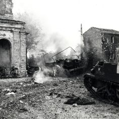 Ortona, Italy. A jeep and a 15-cwt. truck of the Seaforth Highlanders of Canada are set alight by mortar fire, 23 December 1943. The church at the left of the picture was being used as company headquarters. (Photo by Terry Rowe, LAC a170291.)