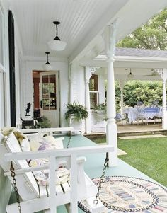 via The Porch Potatoes~  Wraparound Porch-  The 16- by 20-foot porch runs along a new addition. The owner can host a crowd there for meals under the shade of a beadboard-lined ceiling. Antique schoolhouse lamps offer light at night.  CountryLiving.com
