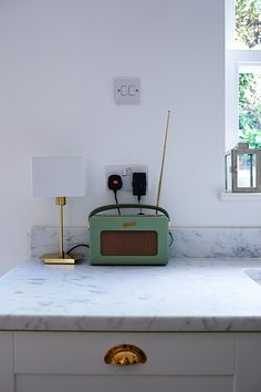 Green Roberts Radio in on Cararra Countertops in kitchen of Gold Perrins & Rowe faucet in butler sink, Cararra Marble countertop in kitchen of Isabel and George Blunden London renovation | Remodelista