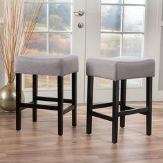 """Simple, yet stylish, this 25"""" bar stool is an understated addition to any home bar or dining ensemble. Made from solid rubberwood in a glossy black finish, this charismatic design features cushioned polyester upholstery, a contoured seat, four straight legs and a footrest. Hosting friends from out of town this weekend? Serve up a casual breakfast on the kitchen island before showing them the sights about town. Seat your guests in these chic stools with a hot mug of coffee while you&..."""