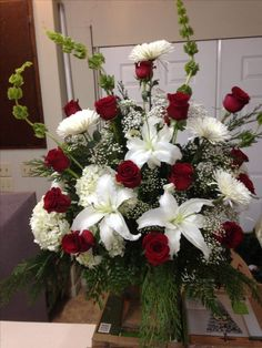 Fresh church arrangement using bells of Ireland, white lilies, white hydrangeas, white spider