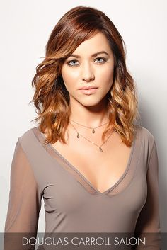 Shoulder-length waves are enhanced with ombré, featuring chestnut brown hues with red undertones cascading into dark caramel strands.