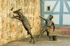 """Bronzefiguren """"Hütejunge""""  Standort: Querweingasse/Stadtmauer (Rotenburg an der Fulda)  Auf der Wiese zwischen Stadtmauer und der Fulda, die in ihrem  ursprünglichen Flussbett nicht weit entfernt entlang floss, wurden noch  nach dem letzten Weltkrieg die Ziegen gehütet. Auf dem Weg zur  Weide hat dieser Knabe mit seiner störrischen Ziege zu kämpfen, die  in der alten Stadtmauer ein Bündel gewachsenes Gras entdeckt hat."""