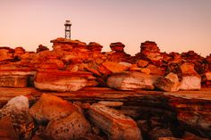 Planning to visit Broome, Western Australia? Don't miss a sunset at Gantheaume Point. See the sun dip over the ocean and light up the red rocks. For more of the top things to see and do in Broome, check out our easy to follow travel guide with pictures. #broome #westernaustralia #australia #travel
