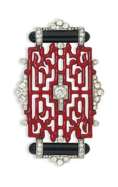 AN ART DECO ENAMEL AND DIAMOND BROOCH, BY CARTIER Of Oriental design, composed of a red enamel openwork panel, with old brilliant-cut diamond centre, mounted between polished onyx baton accents within a further diamond frame, circa 1925, 5.4cm wide Signed Cartier HSA, no.00038