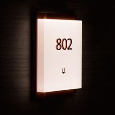 Custom condo number sign from ONE Ala Moana, Oahu, Hawaii. Modern, elegant, and distinctive, we engineered the residence number and doorbell as a solid block of lit acrylic with simple raised numbers sitting on a sleek painted aluminum base. The touch-sensitive doorbell graphic is understated and keeps to the minimalist aesthetic.