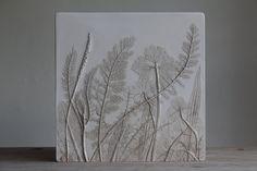 Diese Fliese ist ein original-Stück von Rachel Dein. Um die Fliese, Rachel legten Blumen und Laub auf eine ausgerollte Platte aus Lehm und drückte sie in all ihren Details zu übertragen und anschließend vorsichtig entfernt sie. Ein Holzrahmen war dann über gelegt und der Gips gegossen. Einmal eingestellt, war der Ton entfernt geschält, um die Pflanzen im Relief zu offenbaren. Größe: 25 x 25 x 1,5 cm. Die Fliese hat eine Messingplatte Spiegel auf der Rückseite für eine sichere hängen.