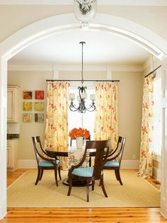Fresh orange floral drapes make this a cheerful dining space