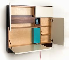the largest panel folds out to serve as a desk suitable for a few papers or a laptop it also houses a charging station hidden behind a turquoise screen