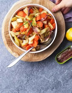 Schil de knolselder en wortelen en snij in grove stukken.Snij de bleekselder in grove stukken.Stoom of kook de groenten beetgaar.Doe de gezouten ansjovisfilet met olie, 1 el olijfolie, zeste en sap van de citroen in een pan.Laat de ansjovis in de citroenolie op een zacht vuur smelten.Voeg de beetgare groenten bij de olie en meng.